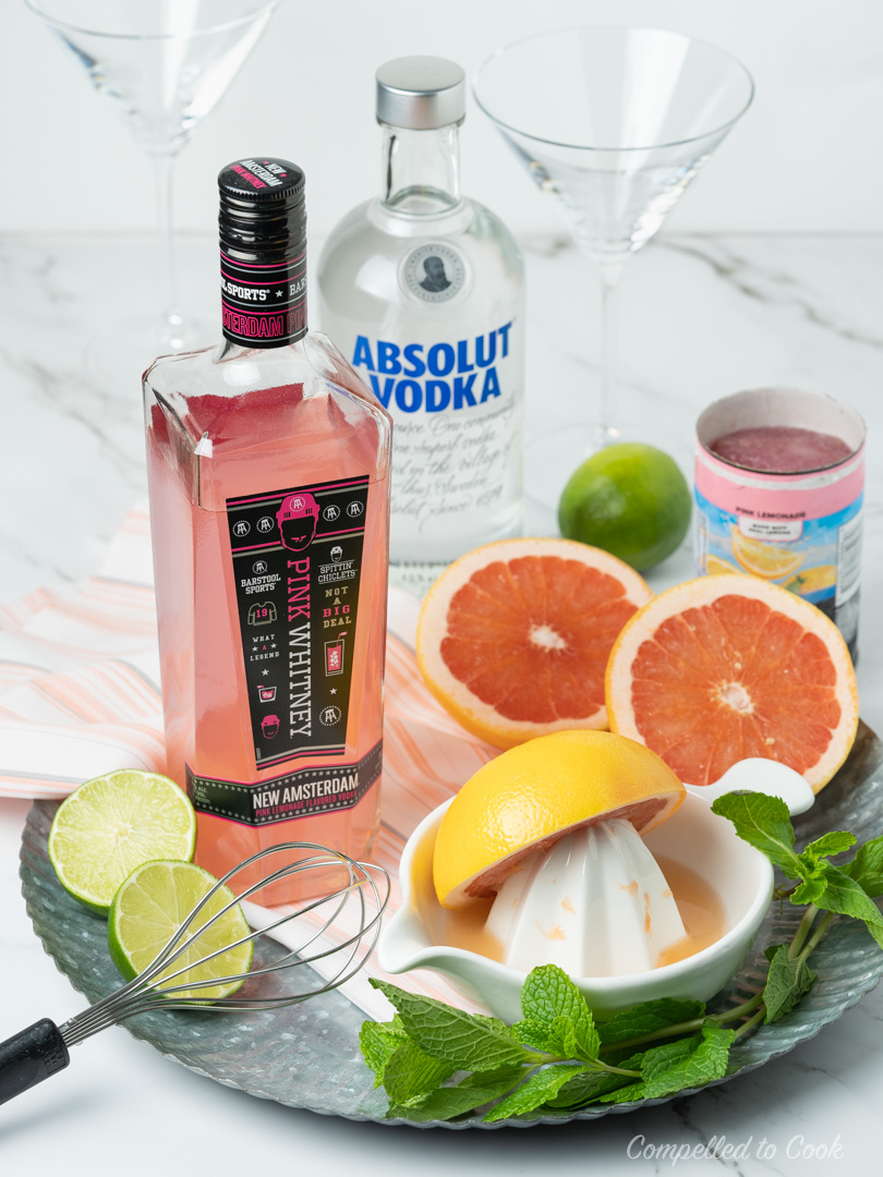 Ingredients for Pink Whitney Slush on a sliver tray garnished with fresh mint leaves.