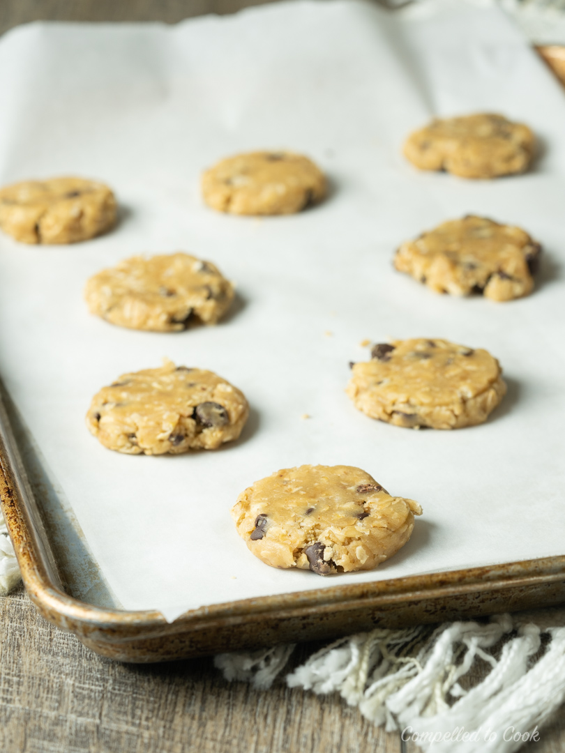 A parchment lined baking tray filled with flattened cookie dough balls in making Chocolate Chip Oatmeal Cookies.