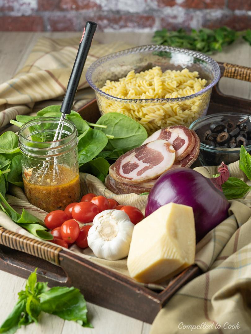 Ingredients for Mediterranean Pasta Salad arranged on a wodden tray.