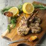Grilled Lamb Chops arranged on a wooden board and garnished with fresh lemon, herbs and red pepper jelly.