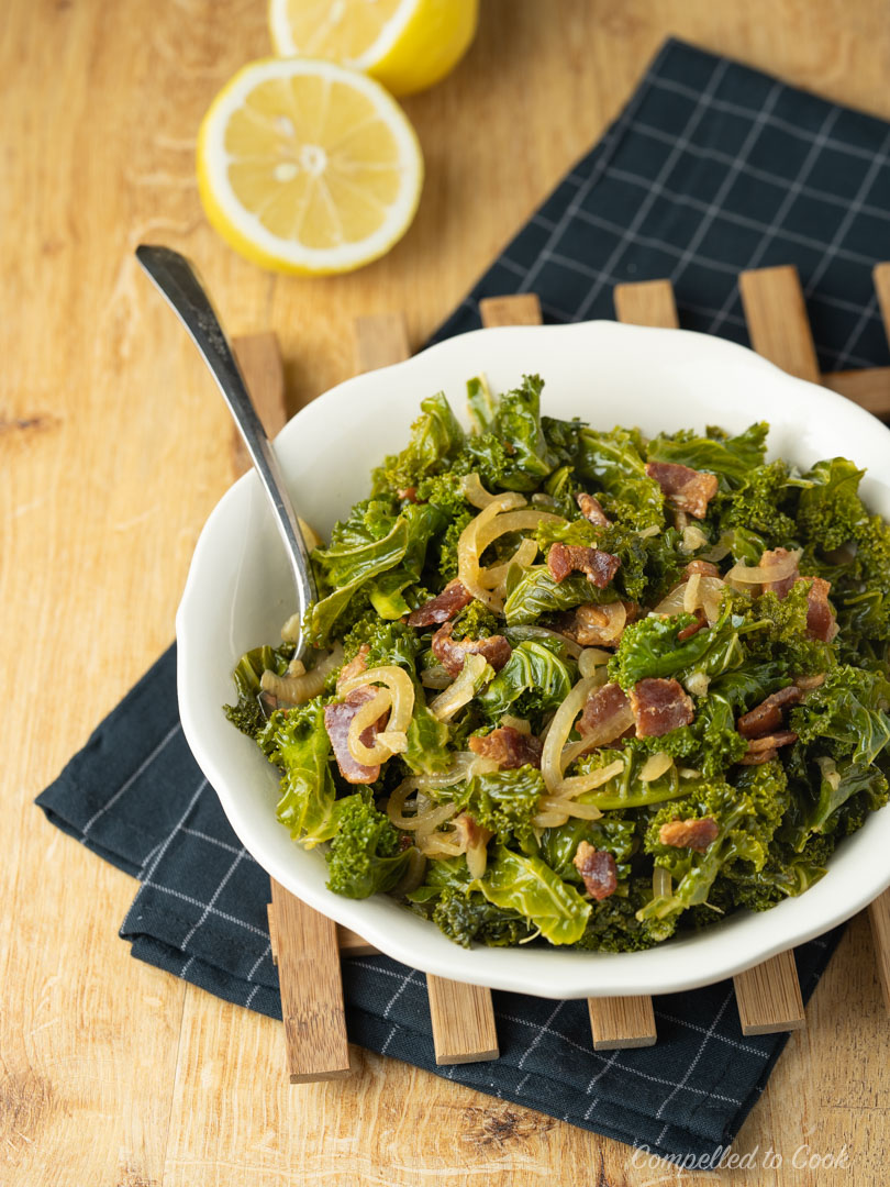 Braised Kale with Bacon served in a shallow white bowl resting on a wooden trivel and blue checkered kitchen towel.