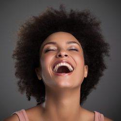 A beautiful woman laughing on a gray background