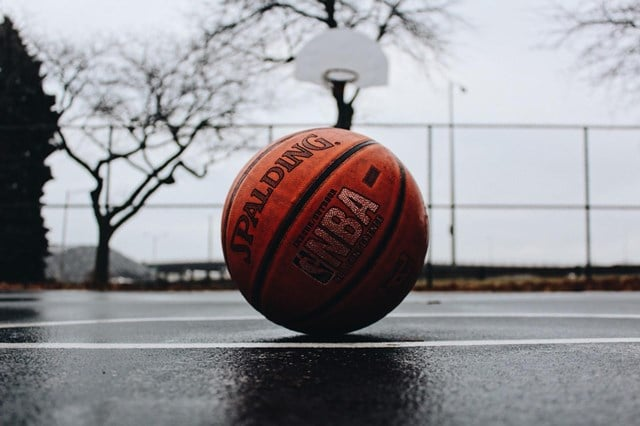 Closeup of an NBA basketball on an outside basketball court in rainy weather