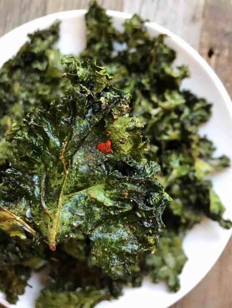 Close-up shot of a Crispy Baked Kale Chip above a plate of chips