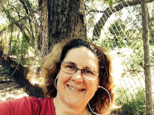Laurie in a red t-shirt under a tree.