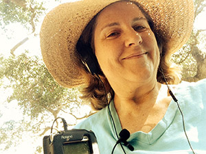 Laurie with two mics wearing headphones along with her floppy hat under the trees.