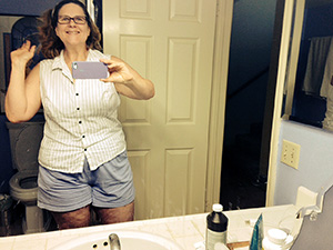 Laurie takes a photo of herself wearing shorts in the mirror.