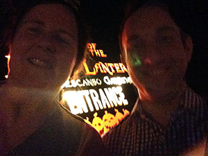 Laurie and Steve stand in front of the Rise of the Jack O'Lanterns sign