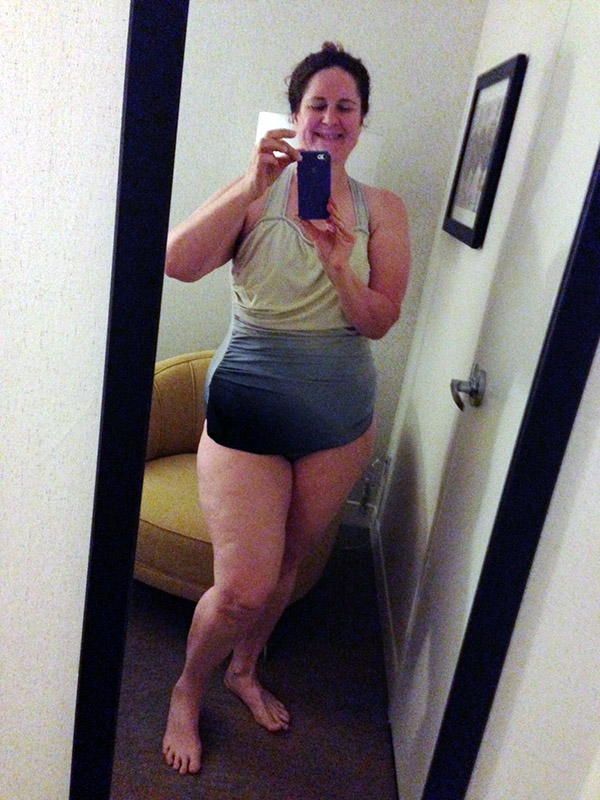 Laurie in full length mirror in a one piece swimsuit