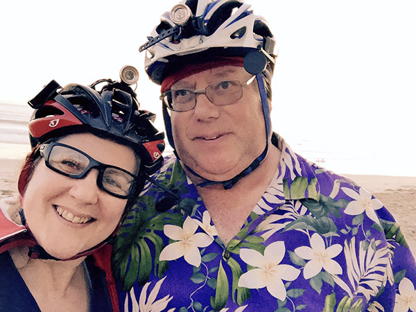 Laurie and Mark in bike helmets pose in front of the beach. Mark wears a purple flowered Hawaiian shirt