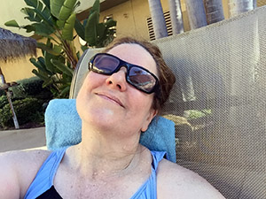 Laurie in a swimsuit in a chair by the pool