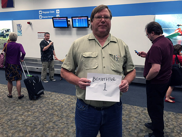 Mark holding a sign like a limo driver saying Beautiful 1 at the airport waiting area