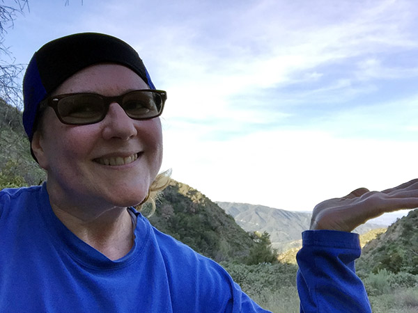 Laurie indicates the view of the valley below the mountain trail with an open hand gesture