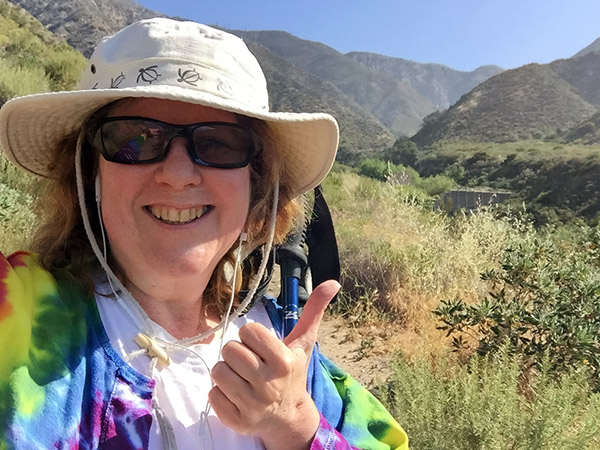 Laurie on the hiking trail on a sunny day giving thumbs up.