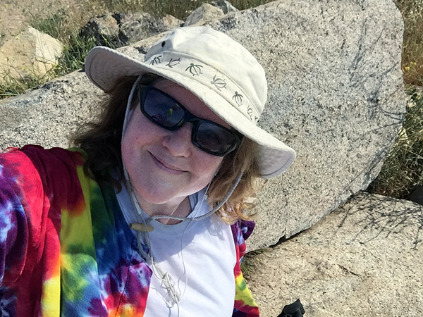 Laurie rests on a natural bench formed by two large rocks.