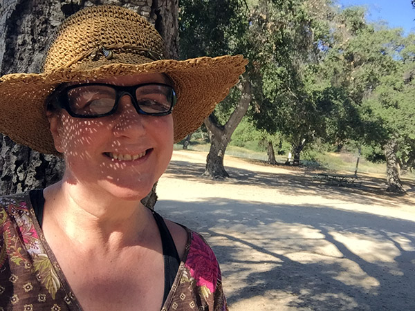 Laurie in a straw hat by a tree