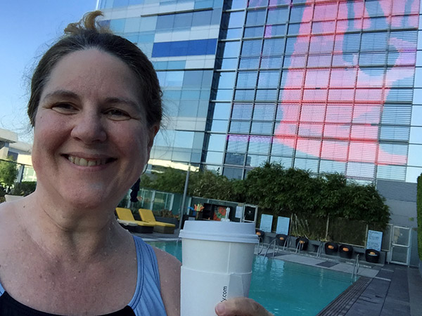 Laurie holding coffee by the pool with neon sign in back