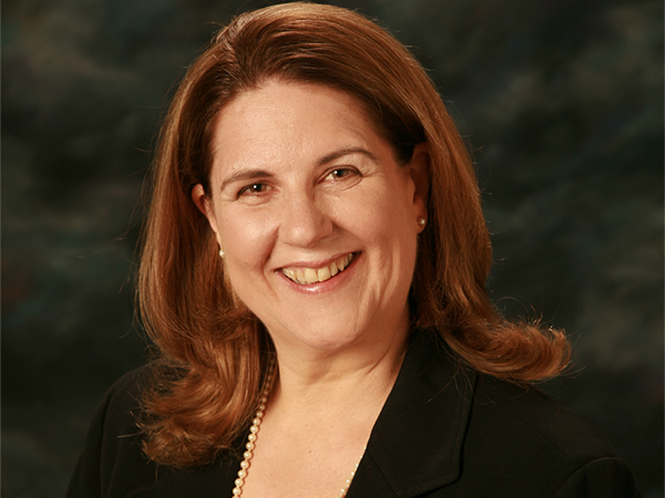 Laurie with styled long hair in suit and pearls - corporate headshot