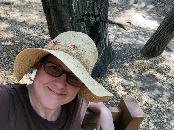 Laurie in her sunhat sitting on a bench by an oak tree trunk