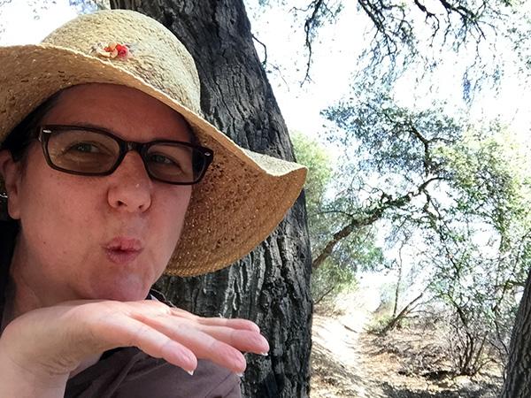 Laurie blows a kiss near an oak tree
