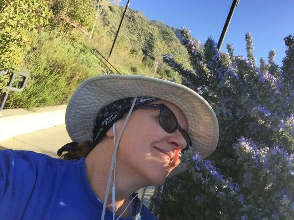 Laurie smelling wild rosemary on a hike