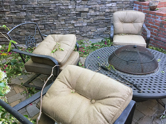 Fire pit area in complete disarray with cushions tossed, leaves everywhere, branches leaning on everything