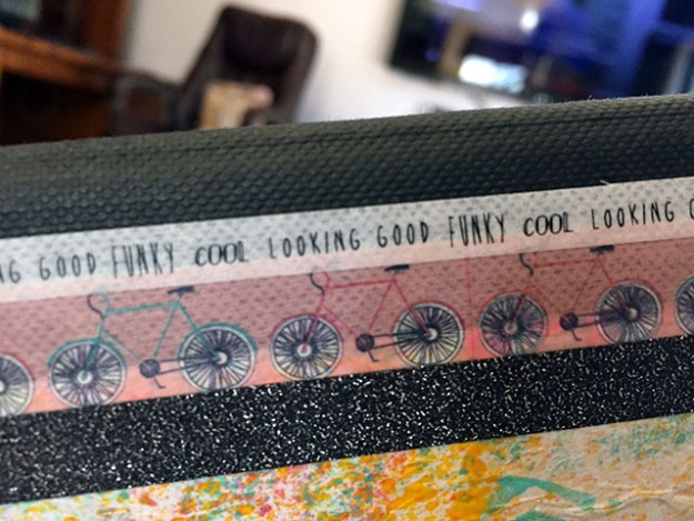 Hand made book binding shown close up with a pattern of bikes and words like looking good and funky cool