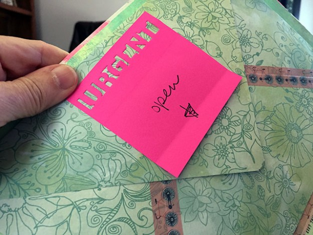 Pink sticky labeled urgent points to an envelope pasted within the journal that contained a card
