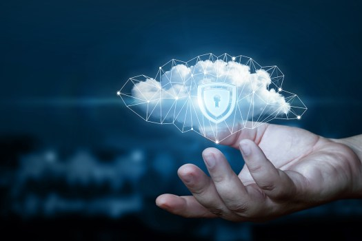 Hand shows a data cloud with a protective shield for cloud firewall