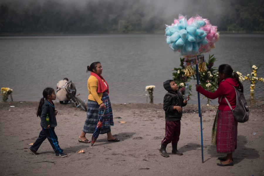 A woman sells cotton candy at the shores of lake Chicabal, forty days after the end of holy week, in a sincretic ritual aimed to bring rain. Photo: Santiago Billy/Comvite