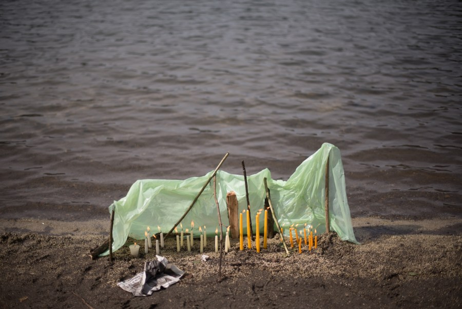 Lit candles protected by a plastic shelther on the shores of lake Chicabal. Photo: Santiago Billy/Comvite