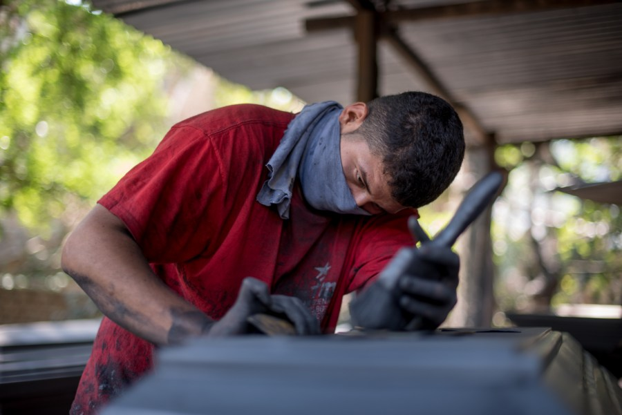 A young man gives finishing touches to the sealer before sending the casket to painting. Jucuapa, El Salvador