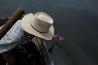 A local fisherman on his canoe picks up trash from Lake Atitlán, Sololá, Guatemala.  Photo: Jeff Abbot/Comvite