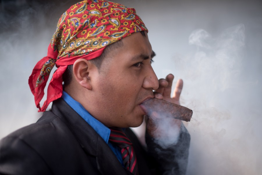 A man smokes a cigar, these cigars are believed to have medicinal properties and are usually smoked on a single sitting. Photo: Santiago Billy/Comvite