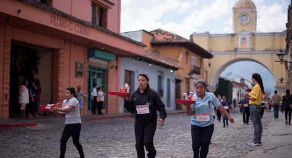 Runners in the women division struggle with trays during the race in La Antigua Guatemala. Photo: Santiago Billy/Comvite