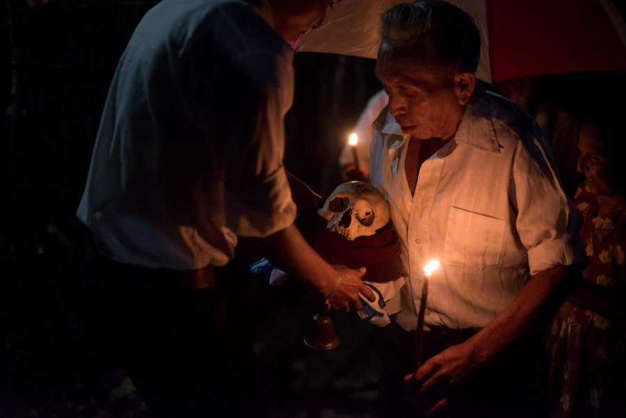 A faithfull returns the skull back to the procession after paying respects in their family home. San José, Petén, northern Guatemala. Photo: Santiago Billy/Comvite