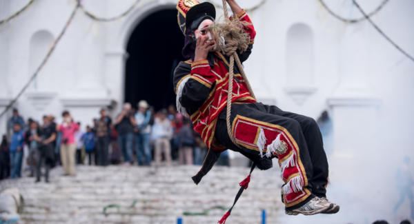 "A traditional dancer holds his mask as he descends from ""El Palo Volador"". Photo: Santiago Billy/Comvite"