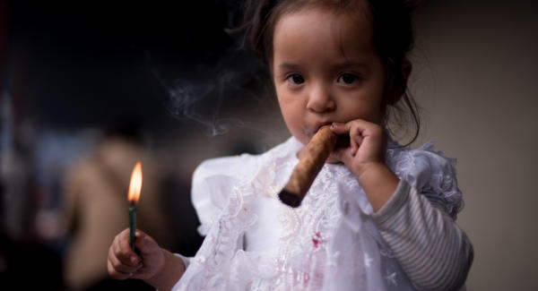 "Ginger Casambrita Cabrera Atz, smokes a cigar during the celebrations of the ""birthday"" of San Simón, a local sincretic Saint in San Andrés Itzapa. Photo: Santiago Billy/Comvite"