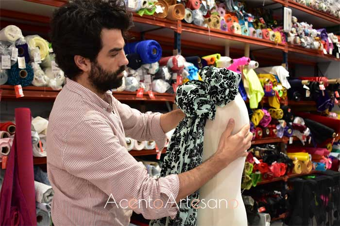 Felipe colocando uno de los tejidos de la temporada en un maniquí