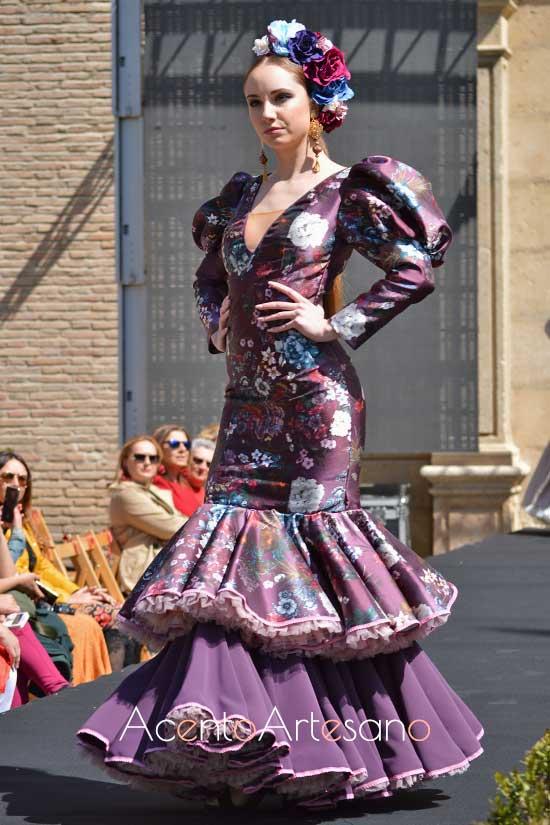 Traje de flamenca en tono berenjena con flores  de Rebeca Moda Flamenca