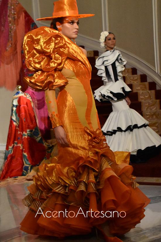 Traje de flamenca de talle bajo en naranja y asimetría en mangas de Francisco Tamaral para Úniqo Qlamenco