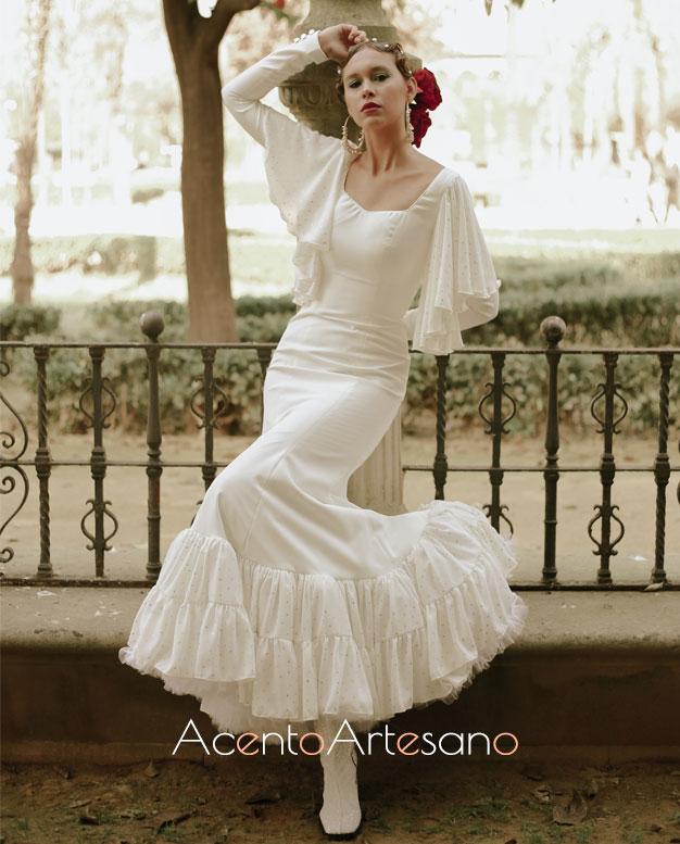 Traje de flamenca blanco de Aurora Ruíz con mangas de capa y vuelo evasé acabado en volantes canastero