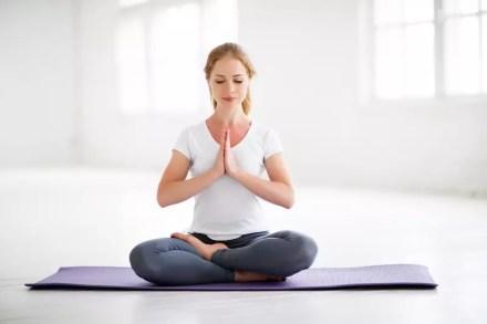Frau sitzt auf einer Matte und meditiert. Meditation ist gerade bei Erwachsenen ein häufig gewähltes Mittel zur Konzentrationssteigerung
