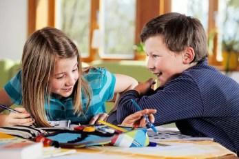 Zwei Kinder raufen sich spielerisch beim Malen