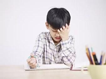 Ein Junge sitzt frustriert über einem Heft und hält sich den Kopf.