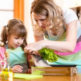 Mutter und Tochter beim Kochen: Omega-3-Fettsäuren sind insbesondere in Fischöl enthalten
