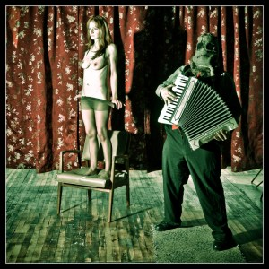 scarecrow playing accordian with nude model on chair