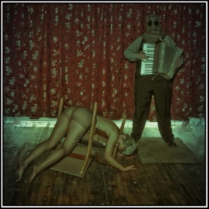 scarecrow playing accordian with model draped over chair