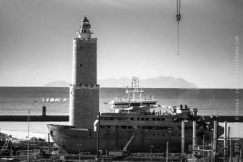 Faro e nave davanti al porto