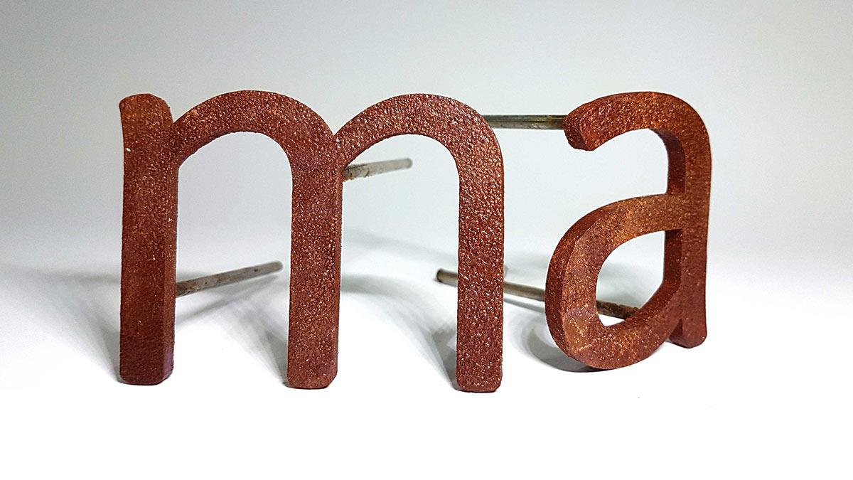 Primer plano de letras en acero corten realizado por Láser Mallorca.
